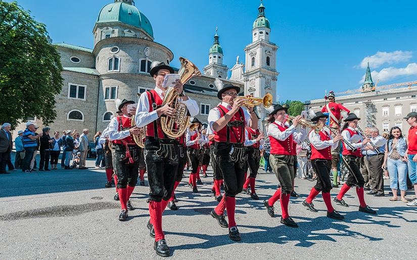 נגנים בלבוש אוסטרי מסורתי צועדים ומנגנים במרכז זלצבורג